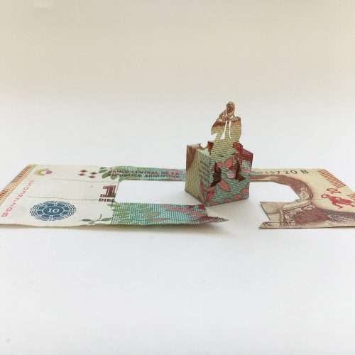 Installation of a man holding a mobile phone, made with cut and folded Argentinian banknote.