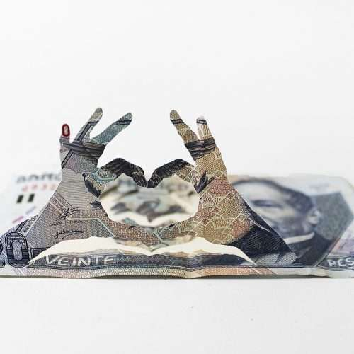 Papercutting depicting hands in heart shape, made from Mexican banknote.