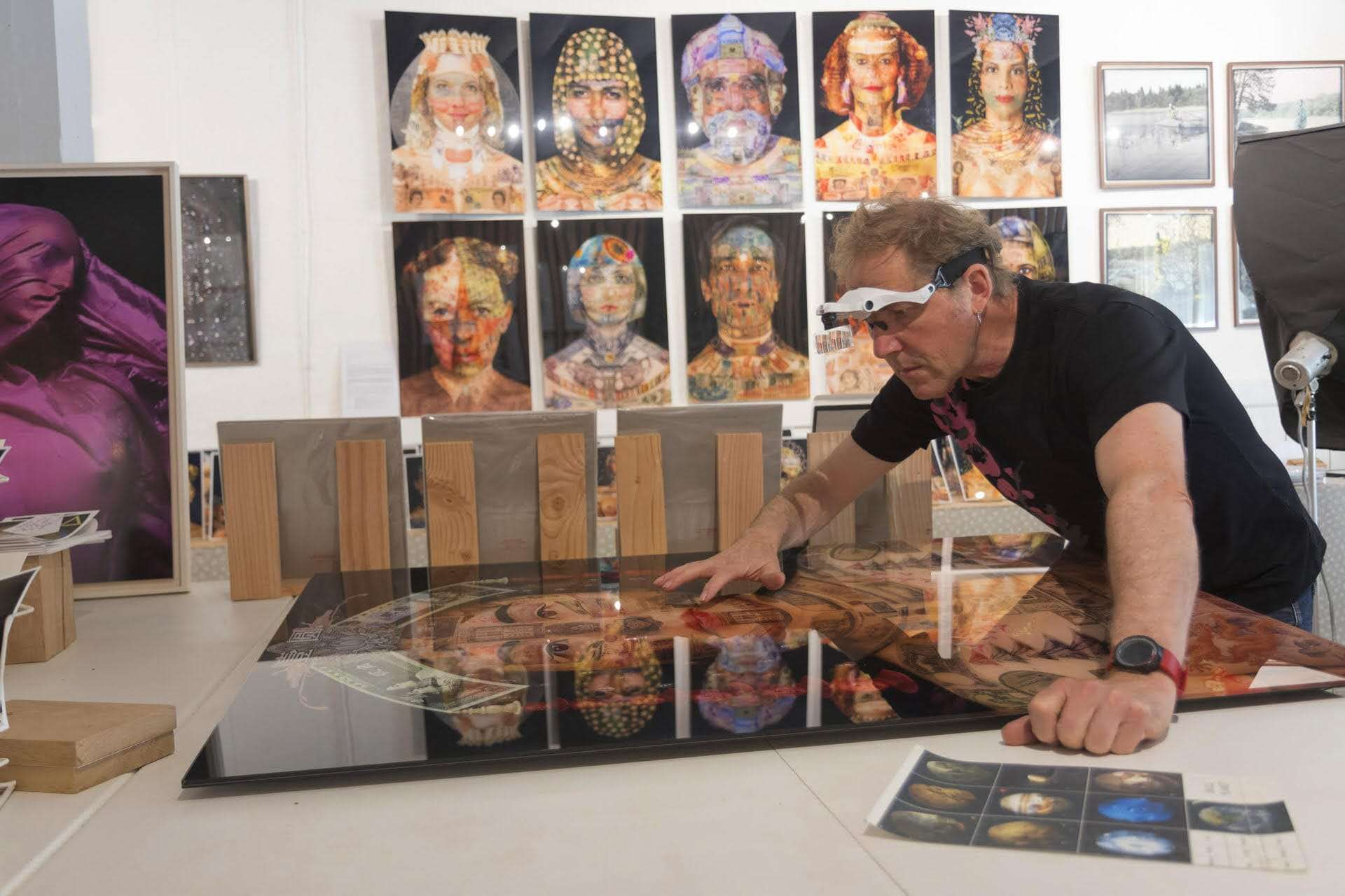 Artist Philippe Assalit in his workshop with some of his creations on the wall behind him.